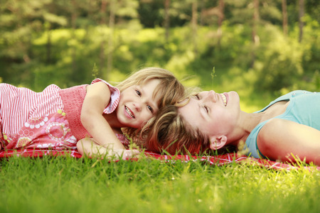a Mama and her little daughter playing on grass  photo