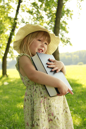 a beautiful little girl with the Bible in nature  photo