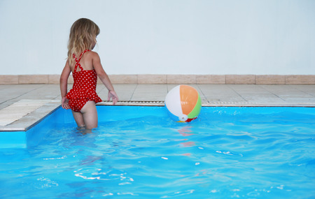 a little girl playing in the pool  photo