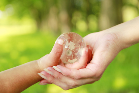 human rights: a glass globe in the hand of a parent and child