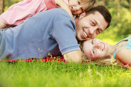 a young family with little daughter lie on the grass photo