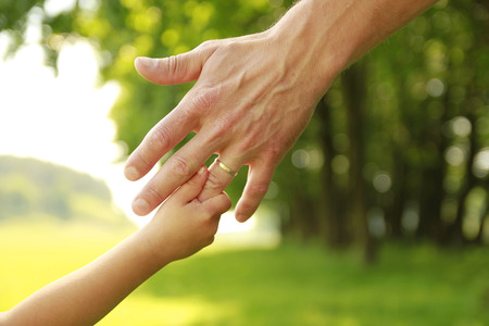 responsibility: a hand of parent and child in nature Stock Photo
