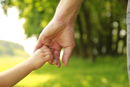 a parent holds the hand of a small child photo