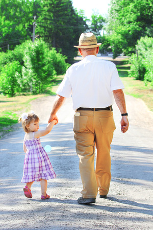 a grandfather with his granddaughter are on the road  写真素材