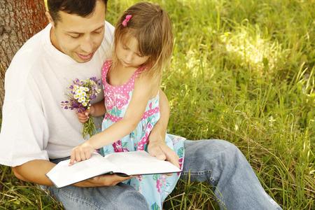 聖書を読み、彼は小さな娘を持つ若い父 写真素材