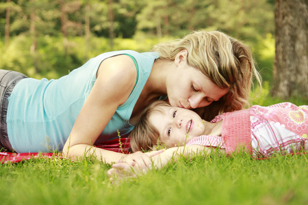 a Mama and her little daughter lie on the grass photo