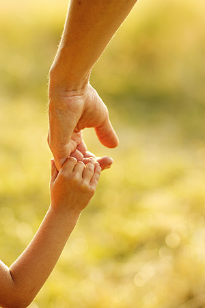 a parent holds the hand of a small child 写真素材