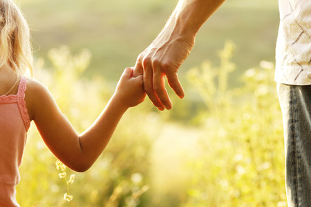 quiet adult: a parent holds the hand of a small child Stock Photo