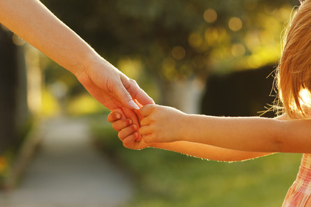 family with two children: a parent holds the hand of a small child Stock Photo