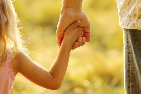 in custody: a parent holds the hand of a small child Stock Photo