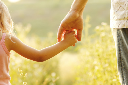 old hand: a parent holds the hand of a small child Stock Photo