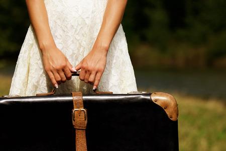 femme valise: une main d'une jeune femme avec une valise Banque d'images