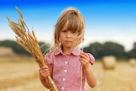 a little girl on the field with wheat