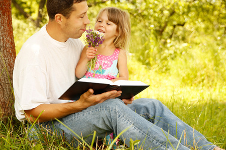 church people: a young father with his little daughter reads the Bible
