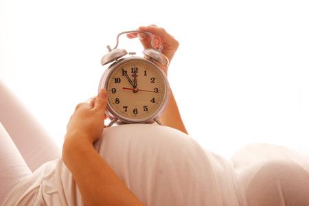 白い背景の上の目覚まし時計で妊娠中の女性