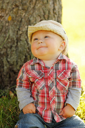 a little boy in a cowboy hat playing on nature photo