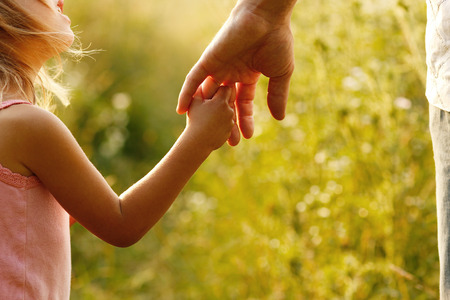 child: a parent holds the hand of a small child Stock Photo