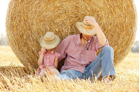 a little girl with her father on the field with wheat