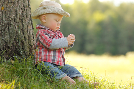 a little boy playing in a cowboy hat on nature 写真素材