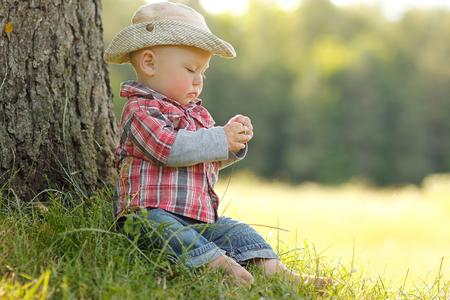 自然にカウボーイ ハットで遊ぶ少年