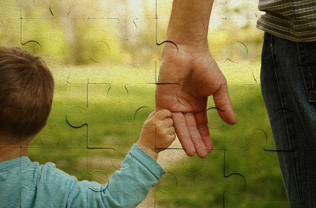 out of production: the parent holds the hand of a small child on piece of puzzle Stock Photo