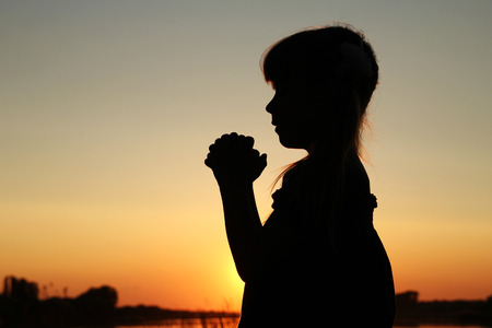 christian young: silhouette of a little girl praying