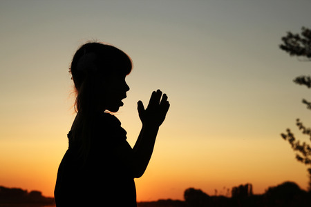 pray: a nice silhouette of a little girl praying