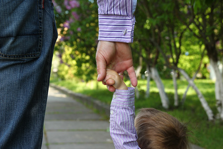 the parent holds the hand of a small child Stock Photo
