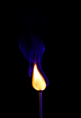 firestarter: fire and smoke from the burning match in the dark Stock Photo