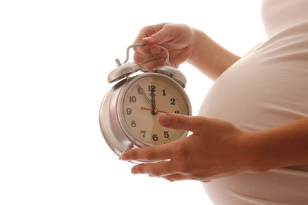 convulsions:   Pregnant woman with clock on a white background