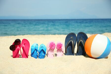 Family slippers on the sand on the beach with ball and sunglass
