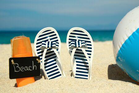 Family slippers on the sand on the beachin summer Reklamní fotografie