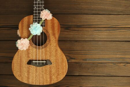 Ukulele musical instrument on wooden background
