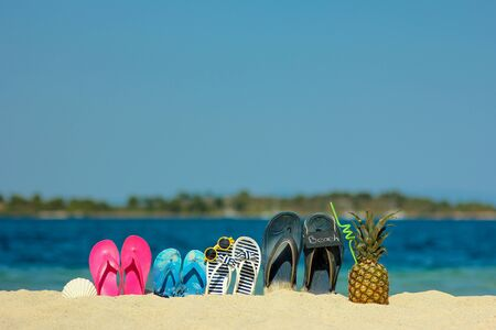 Family slippers on the sand on the beach in summer