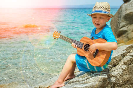 happy child playing guitar by the sea greece on nature background Zdjęcie Seryjne
