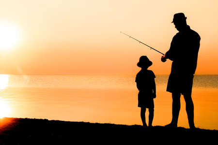 Happy father and child fishermen catch fish by the sea on nature silhouette travel