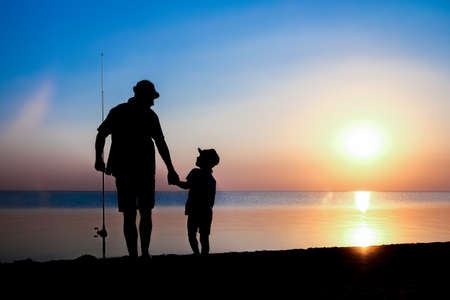 Happy father and child fishermen catch fish by the sea on nature silhouette travel 版權商用圖片