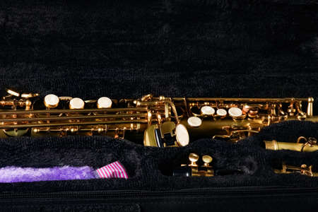 soprano saxophone in a case on a black background