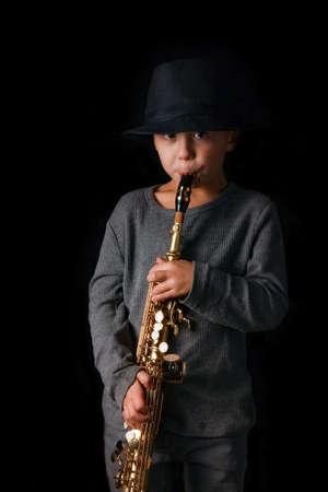 happy child plays saxophone in studio