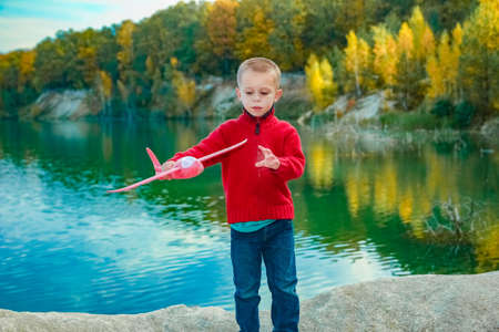 Happy child launches an airplane in nature in the park