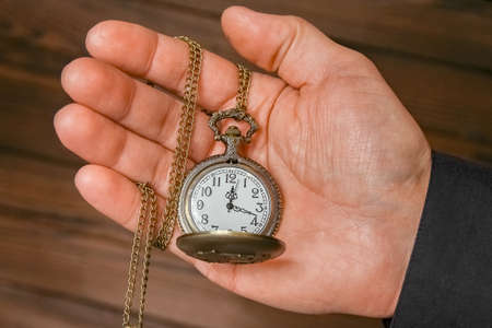pocket watch in the hands of a man