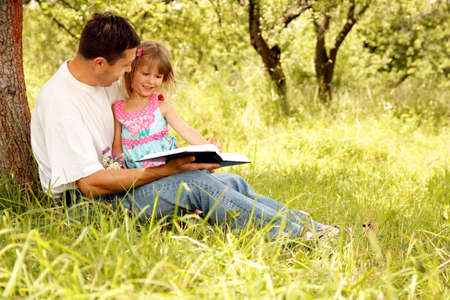 Happy parents with a child read the Bible in the nature park