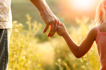 hands of parent and child outdoors in the park Archivio Fotografico