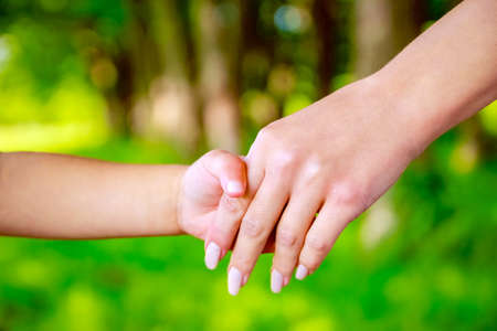 hands Happy parents and child outdoors in the park Archivio Fotografico