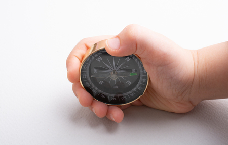 Compass tool in toddler hand on white