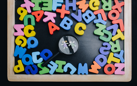 Kids under Magnifying glass and Colorful Letters of Alphabet