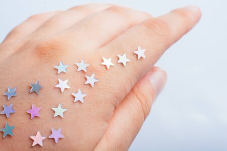 Little bright stars on a on hand on gray background Banque d'images