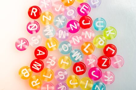 Multi color alphabet letter beads placed randomly on white background