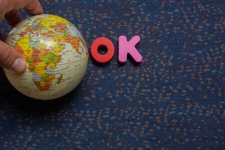 Hand holding globe model beside word OK