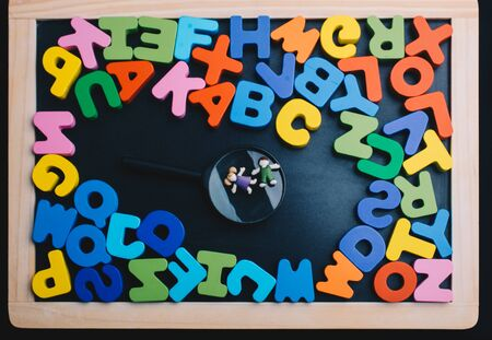 Kids over Magnifying glass and Colorful Letters of Alphabet